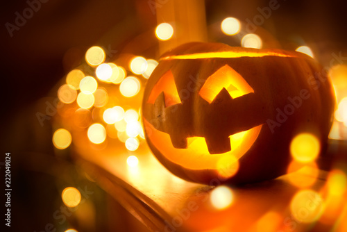 Leinwanddruck Bild A cheerful smiling Jack O Lantern on halloween placed on a fireplace with fairy lights