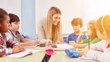 Gruppe Kinder macht Hausaufgaben in Ganztagsschule - 222053413