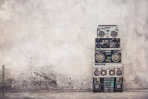 Retro old school design ghetto blaster boombox  stereo radio cassette tape recorders tower from circa 1980s front concrete wall background. Vintage style filtered photo - 222057693