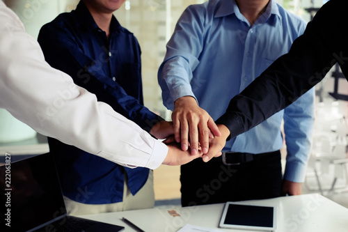 Foto Murales Business people putting their hands on top of office desk cooperation concept.
