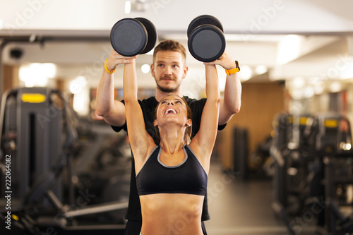 girl with fitness coach lifting weights - 222064082