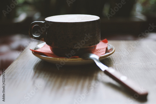Naklejka Cup of hot coffee on table in cafe backlit - vintage dark color tone with shadows up