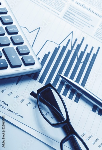 Calculator, Pen and Eyeglasses on Business Graphs - 222069264