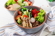 Buddha bowl dish with chicken fillet, quinoa, avocado, sweet pepper, tomato, cucumber, radish, fresh lettuce salad and sesame. Detox and healthy superfoods breakfast bowl concept. - 222079204