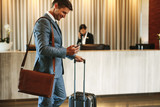 Businessman arriving at hotel lobby - 222085673