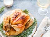 Whole grill chicken with caramelized skin and fresh rosemary on a dinner table. - 222087475