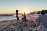 Couple proposing at beach sunset