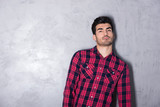 A serious handsome young man in a red checkered shirt standing in front of a grey wall in a studio.