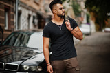 Awesome beautiful tall ararbian beard macho man in glasses and black t-shirt walking against business car. - 222101472
