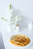 Yummy yellow pancakes on white plate near flowers in white background. Concept of breakfast and food. - 222102649