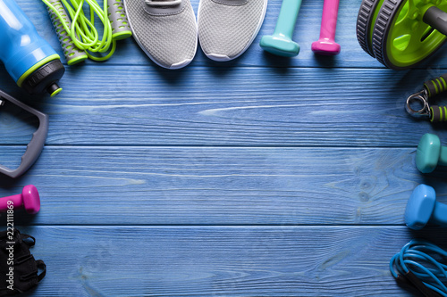Wall mural Fitness equipment - sneakers; jumping rope, water bottle and dumbbell on blue wooden board