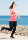 Cheerful girl jogging at seaside