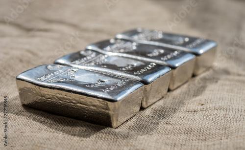 Odlewać srebrne pręty na tle grubej tkaniny o szorstkiej fakturze. Selektywna ostrość.