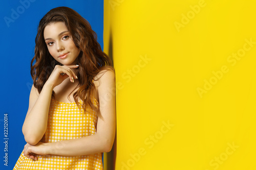 Young woman in yellow sarafan posing near blue background