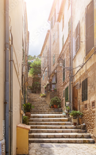 narrow steep alley with steps in historic spanish village on island of Mallorca
