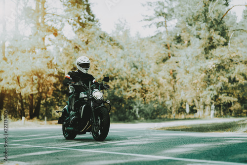 Biker In Helmet Is Riding On Highway In A Forest.