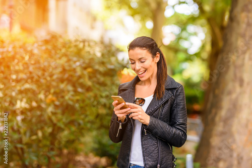 A happy young woman using her phone in a urban environment - 222131842