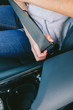 Detail of hand of unrecognizable young woman putting on car's seatbelt