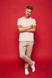 Full length photo of attractive man in striped t-shirt smiling and standing with arms crossed, isolated over red background