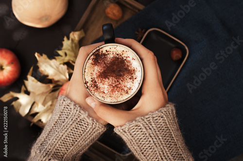 Female  holding cup of pumpkin spice latte coffee, Autumn fall mood, holding hands, top view , warm and cozy. Copy space. - 222150078