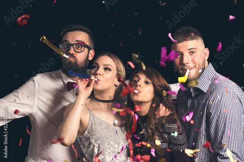 Leinwanddruck Bild Friends blowing party whistles