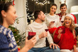 celebration and holidays concept - happy friends with glasses celebrating christmas at home party and drinking red wine