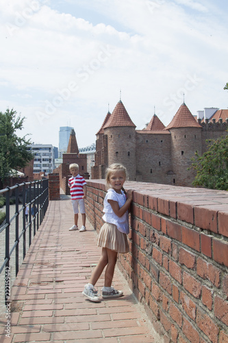 Outdoor portrait of young beautiful boy and girl posing on old street. Old Warsaw, Poland, summer