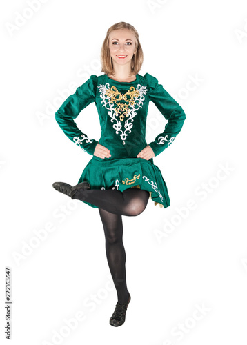 Beautiful young woman in Irish dance green dress jumping isolated