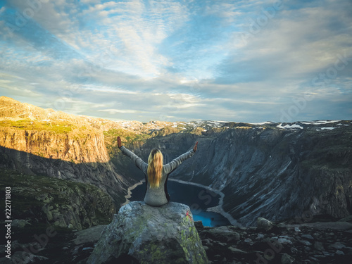 Poster Young woman sitting on stone while relaxing looking at Norway nature. Spring sunny weather with warm colors.Landscape Trolltunga Odda Fjord Norge Hiking Trail