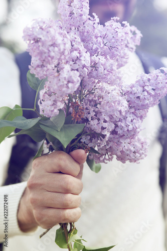Man's hand with bouquet of flowers lilac. Instagram effect, toned photo filter
