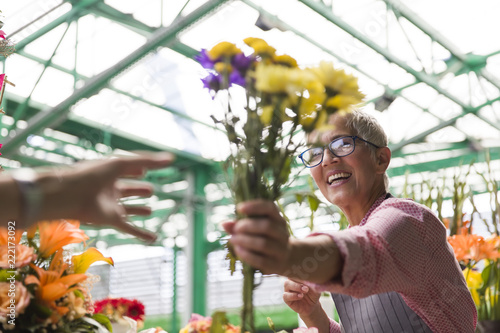 Leinwandbild Motiv Senior woman sales flowers on local flower market