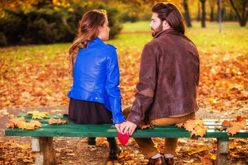 Couple holding heart-shape on a bench in the park.