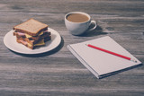 Break at work. Cheese sandwich with cup of white coffee, notebook and pencil. Horizontal view, gray wooden background - 222185655