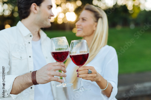 Poster To our future. Glasses with red wine being clinked together by joyful happy couple while having a celebration
