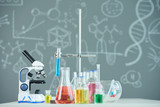 Table in school laboratory with microscope, flasks and test tubes - 222195026