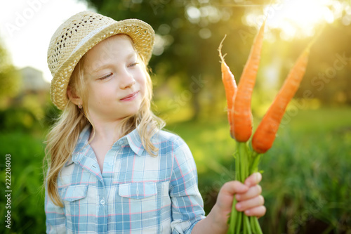 Leinwanddruck Bild Cute little girl wearing straw hat holding a bunch of fresh organic carrots. Fresh healthy organic food for small kids.