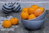 Mandarins and blue decorative balls on gray wooden background. - 222210857