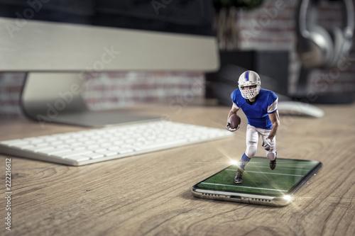Gracz futbolu z błękitnym mundurem bawić się i wychodzi z telefonu komórkowego na pełnym ekranie na drewnianym stole.