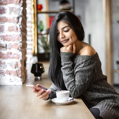 Beautiful girl uses a phone and drinks coffee, sitting in a cozy cafe.