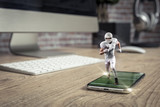 Football Player with a white uniform playing and coming out of a full screen phone on a wooden table. - 222217465