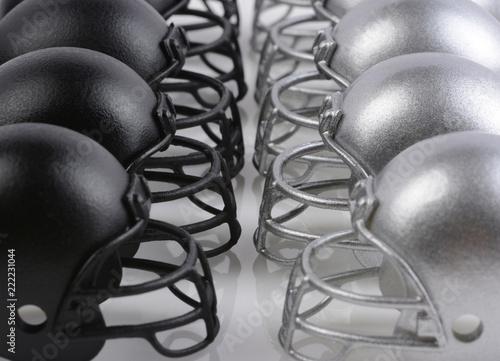 Czarne i srebrne hełmy futbolu amerykańskiego ustawione naprzeciw siebie