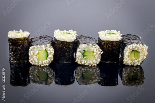 cucumber maki on black background with reflection