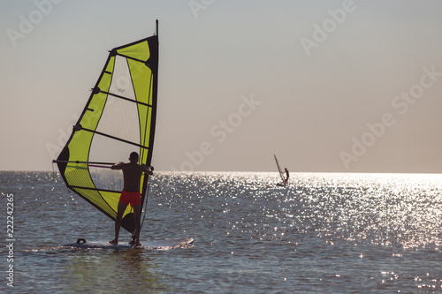 Windsurfers in the sea during sunset, active lifestyle - 222242265