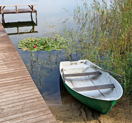 A typical autumn  Lithuanian landscape with a lake  and wooden pier with plastic boat. © Aleksandr Volkov