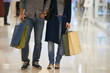 Cropped image of couple with many paper-bags standing in shopping mall - 222254228