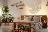 Shadow of a leaf on a wall in a botanical bedroom interior with a comfy double bed. Real photo - 222257638