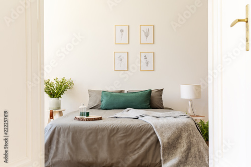 A peek through an open door into a natural sunny bedroom interior with gray and green sheets and cushions on a double bed. Nature drawings on the vanilla wall. Real photo. - 222257619