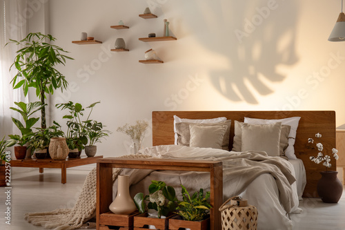 Leinwandbild Motiv Shadow of a leaf on a wall in a botanical bedroom interior with a comfy double bed. Real photo