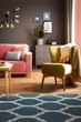Armchair with blanket standing in real photo of dark living room interior with powder pink couch, fresh plant and carpet with moroccan trellis
