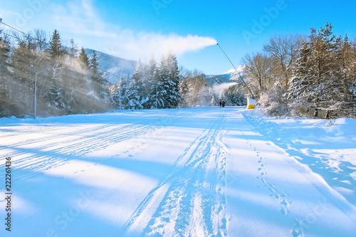 Bansko resort panorama with ski slope, snow cannon working and mountain peaks, Bulgaria